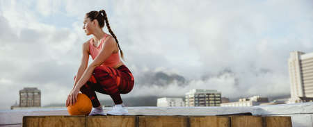 Fit woman wearing sportswear with basketball taking break from workout on rooftop. Female athlete sitting on rooftop relaxing after exercise.