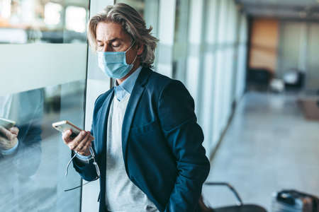 Businessman with face mask standing at airport waiting area using his mobile phone. Male traveler waiting for his flight at airport departure area.