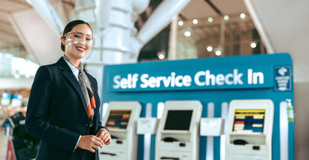Happy young woman working as ground attendant at airport during pandemic. Female airport informational representative standing in front of a self service check in machine at airport looking at camera and smiling. Stock fotó