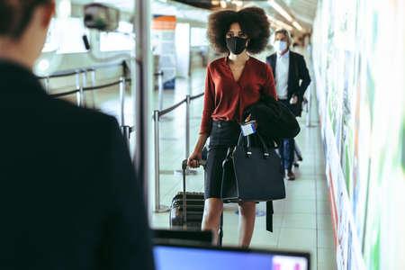 Woman traveler walking through thermal scanning checkpoint at airport terminal. People going through checkpoints at airport during pandemic.
