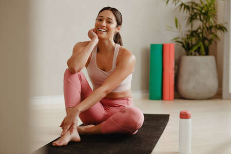 Female in sportswear sitting on yoga mat and smiling after workout. Woman taking a break from workout session at gym. Stock fotó