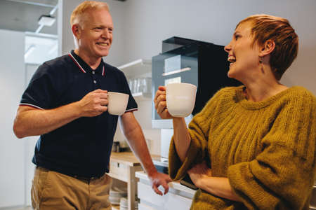 Smiling mature man and woman having coffee break in office. Happy colleagues taking a break from work in office.