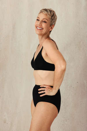 Mature woman embracing her natural and aging body. Confident woman wearing black underwear and smiling cheerfully while standing alone against a studio background. Stock fotó