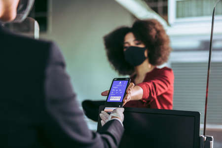 Female traveler wearing face mask showing her boarding pass to ground attendant at check-in counter at airport terminal. Passenger showing her electronic boarding pass on smartphone screen to airline attendant during pandemic.