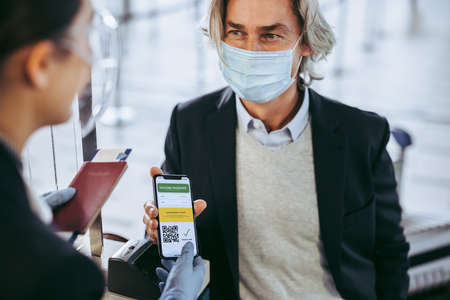 Traveler showing his health passport of vaccination certification on phone to security personnel at airport check in counter. Businessman shows his vaccination passport to ground attendant for check in at airport. Safe travel post pandemic lockdown.