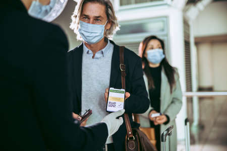 Businessman in face mask showing his covid-19 vaccination passport in mobile phone to ground attendant at airport check-in counter. Passenger showing his vaccination passport to airport informational representative.