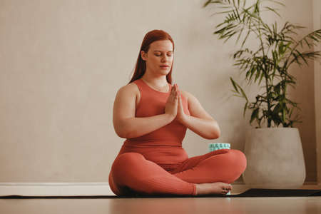 Woman working out at home, doing yoga exercise on mat. Fitness woman meditating in lotus pose.