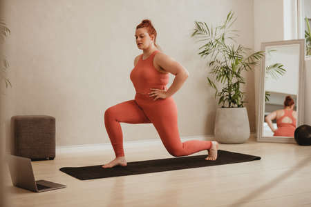Plus size female in sportswear doing lunge workout watching online exercise class. Woman exercising over online workout class on her laptop.
