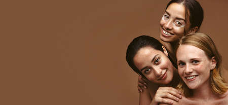 Wide angle shot of three women with skin problems together on brown background. Women having skin problems look happy with their natural skin.