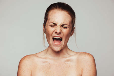 Close up of a frustrated woman with freckles on body. Portrait of woman expressing displeasure and frustration.