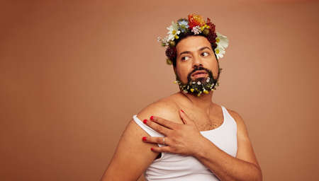 Gender queer wearing tank top and flowers. Non binary person with makeup looking away on brown background.