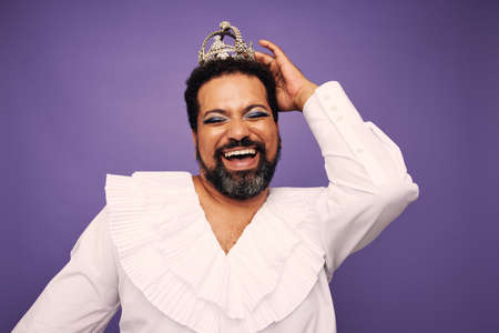 Portrait of a drag queen smiling on purple background. Bearded man wearing makeup and crown on head.