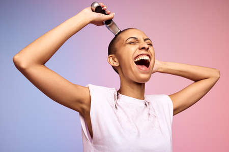 Woman shaving her head and feeling happy. Excited and empowered female after the big chop