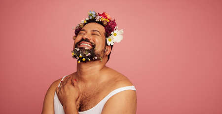 Genderqueer smiling on pink background. Gay man wearing makeup and flowers on head and beard with copy space.