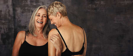 Two mature women in black underwear embracing their natural bodies together. Body positive women smiling cheerfully while embracing each other against a studio background.