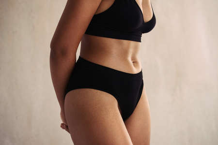 Closeup of an anonymous natural female body wearing black underwear. Young body positive woman embracing her natural body while standing alone against a studio background.