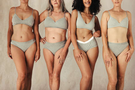 Four natural female bodies of all ages in a studio. Group of body positive and confident women wearing underwear and standing together. Women posing against a studio background.