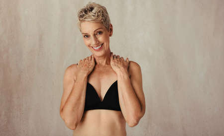 Portrait of a smiling mature woman posing in her natural and ageing body. Confident and body positive woman wearing black underwear and standing alone against a studio background.