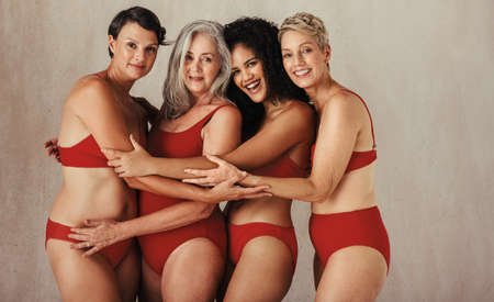 Cheerful women of different ages embracing their natural and aging bodies. Four happy and body positive women embracing each other while wearing red underwear against a studio background.