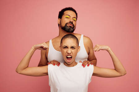 Portrait of expressive friends on pink background. Woman with shaved head flexing her biceps and bearded man with makeup standing behind her.