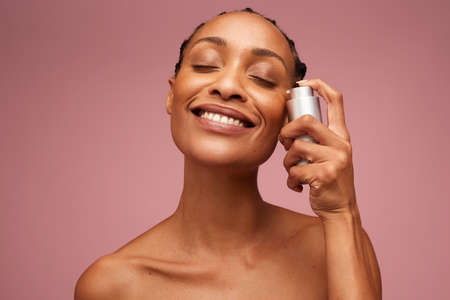 Closeup portrait of a woman with healthy skin using serum on her face. Beautiful woman applying essential oil to her face. Banco de Imagens