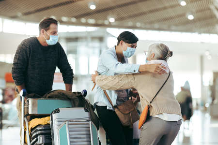 Senior woman meeting her family at airport arrival. Elderly woman welcoming her daughter at airport. All wearing face masks.
