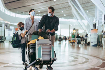 Couple with child standing on luggage trolley at airport in pandemic. Family waiting for their flight at airport in pandemic. Reklamní fotografie