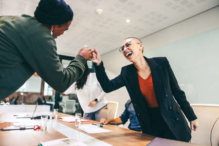 Young businesspeople fist bumping each other before a meeting in a boardroom. Two colleagues smiling cheerfully while greeting each other. Group of businesspeople attending a briefing in a modern office.