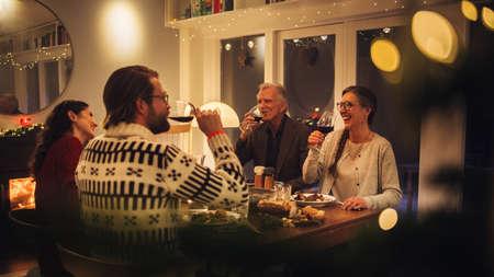 European family sitting at dinner table having wine. Family having thanksgiving dinner at home.