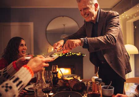 Senior man serving food to family sitting at dinner table. Christmas dinner at scandinavian home.