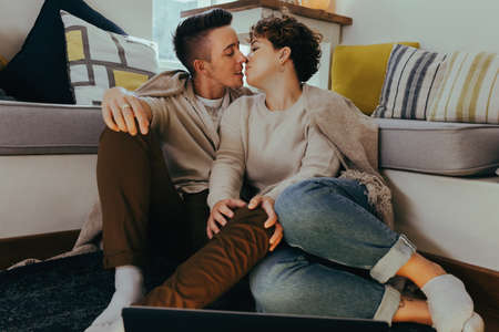 Sweet queer couple going in for a kiss in the living room. Romantic young couple kissing each other while sitting together in the living room. Young LGBTQ+ couple sharing an intimate moment together. Фото со стока