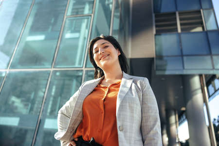Cheerful businesswoman smiling at the camera while standing in front of a high rise office building in the city. Successful female entrepreneur standing alone outside her workplace. Фото со стока