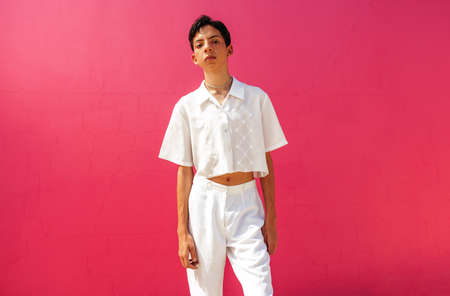 Queer teenage boy standing against a pink background. Young teenage boy looking at the camera while standing in a studio. Confident gay teenager coming out and embracing his identity. Фото со стока