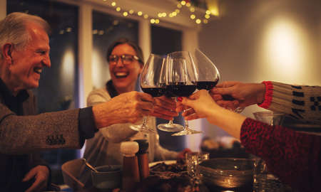 Happy family toasting wine and enjoying dinner on Christmas eve. Family having a Christmas eve dinner together.