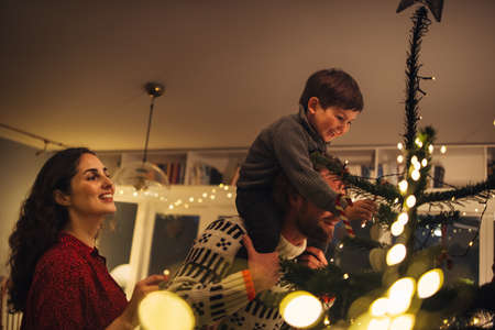 Family decorating a Christmas tree. Young boy sitting on his father's shoulder and hanging lights on Christmas tree. Фото со стока