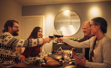 Happy family toasting wine glasses at dining table in the house. Family at dining table for christmas dinner.