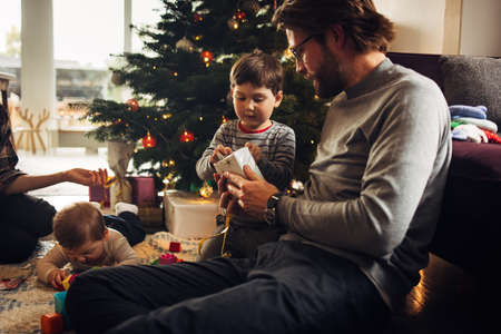 Father and son opening Christmas gifts. Family sitting in living room by Christmas tree unwrapping presents.
