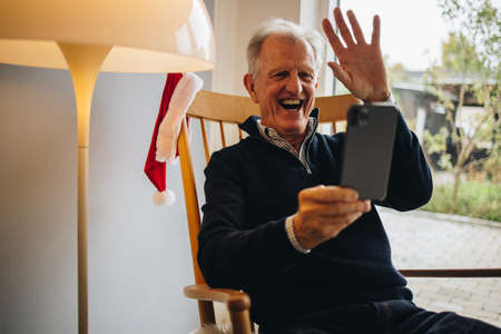 Happy senior man connecting with loved ones over a video call during Christmas. Christmas greeting over a video call.