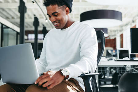 Smiling businessman working on a laptop in a modern office. Happy young businessman enjoying working alone in a modern workplace. Creative young businessman working on a new project.