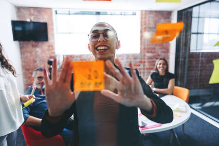 Smiling businesswoman sticking adhesive notes to a glass wall with her colleagues in the background. Happy young businesswoman sharing her ideas with her team in a modern office.