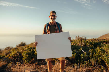 Hiker holding a blank placard on a hilltop. Happy mature backpacker displaying a banner while standing on top of a hill at sunset. Adventurous male activist smiling at the camera. Фото со стока