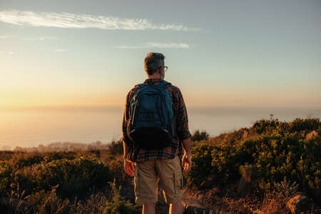 Anonymous backpacker looking at the panoramic view on a hilltop. Rearview of a male hiker standing alone on a coastal hill. Adventurous mature man enjoying the sunset outdoors. Фото со стока