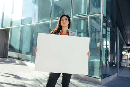 Confident businesswoman holding a blank banner and looking at the camera while standing in front of a high rise office building in the city. Business activist standing alone outside her workplace.