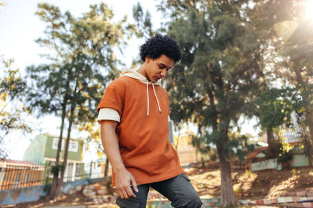 Sporty teenage boy playing with his skateboard in an urban park. Carefree skateboarder standing alone outdoors during the day. Teenager skateboarding in his leisure time.
