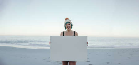 Cheerful winter bather smiling at the camera while holding a white banner at the beach. Female activist displaying a blank placard. Middle aged woman standing by the sea in swimwear.