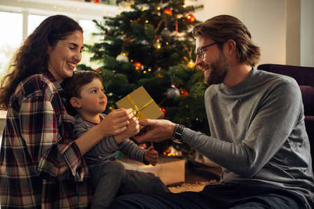 Man giving Christmas gift to his son and wife. Family sitting in living room exchanging Christmas presents.