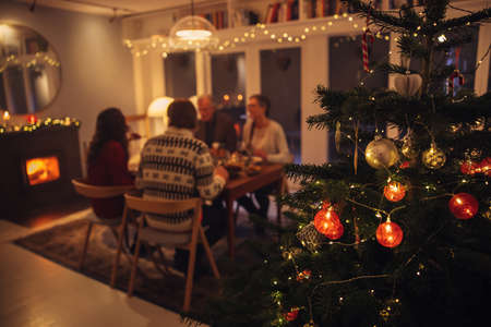 Interior shot of warm and cozy scandinavian home decorated for Christmas celebration. Focus on decorated Christmas tree with family sitting at dinner table having a Christmas eve dinner in background.
