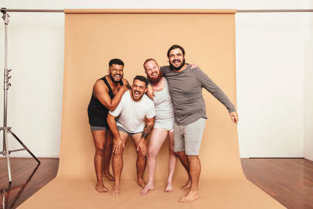 Male friends laughing cheerfully in a studio. Four body positive men having fun while standing together. Group of self-confident young men feeling comfortable in their natural bodies.