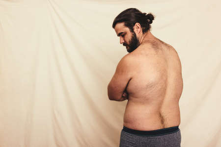 Flexing everything natural. Rearview of a shirtless young man wearing underwear in a modern studio. Self-confident and body positive young man embracing his natural body.