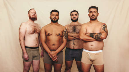 Four young men standing shirtless against a studio background. Group of body positive young men wearing underwear in a studio. Self-confident young men embracing their natural bodies. Фото со стока